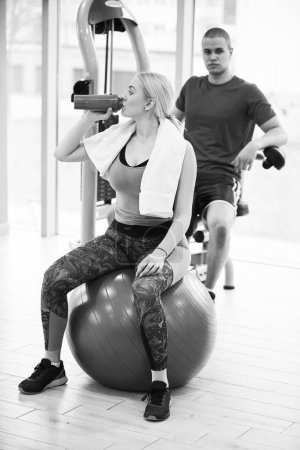 Photo for Professional bodybuilding athlete relax after exhausting training. Athlete relax and drink water from sport bottle in gym interior. - Royalty Free Image