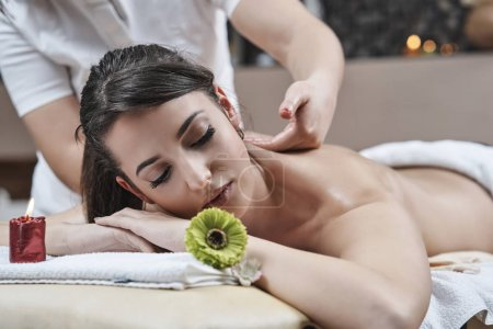 Photo for Woman enjoying relaxing back massage in cosmetology spa centre . - Royalty Free Image