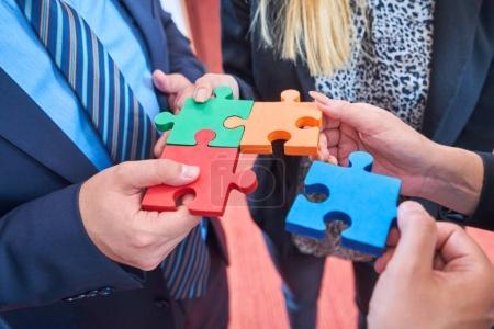 Foto de Grupo de empresarios, armar rompecabezas y concepto de apoyo y ayuda de equipo representan en oficina moderna - Imagen libre de derechos