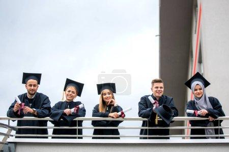 Photo pour Groupe de divers International diplômé étudiants célébrant, assis ou debout, concept - image libre de droit