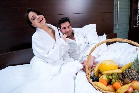 Photo for Couple relaxing in bed with fruit basket, pleasure - Royalty Free Image