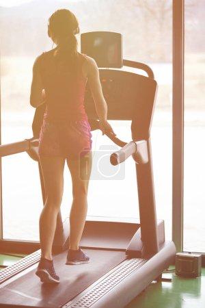 Photo for Girl runs on treadmill. Active girl in gym runs on treadmill. Athlete cardio activity on treadmill. - Royalty Free Image