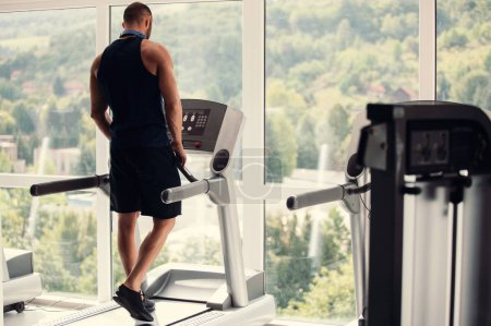 Photo for Young man in sportswear running on treadmill at gym - Royalty Free Image