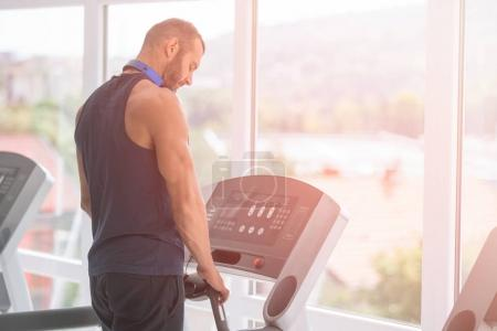 Photo pour Jeune homme en vêtements de sport courir sur tapis roulant à la salle de gym - image libre de droit