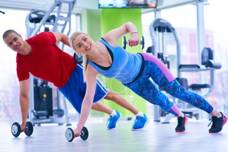 Photo pour Femme de formation avec instructeur de conditionnement physique au gym - image libre de droit