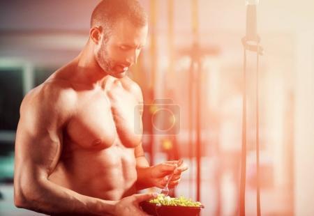 Bodybuilder eating salad in the gym