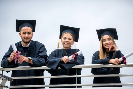 Photo for Group of Diverse International Graduating Students Celebrating, sitting and standing, concept - Royalty Free Image