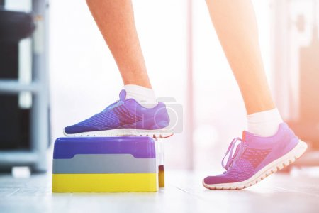 Photo for Athletic woman trainer doing aerobic class with steppers to people group on a modern fitness center. Sport and health concept. - Royalty Free Image