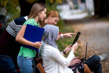 Photo pour Groupe de jeunes gens à l'aide d'ordinateurs portables et tablet sur un banc de parc, s'amuser, parler, sortir - image libre de droit