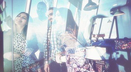 Foto de Concepto de negocio, Inicio, planificación, gestión y personas - equipo creativo feliz escribir en etiquetas engomadas en el tablero de cristal de oficina en oficina moderna - Imagen libre de derechos