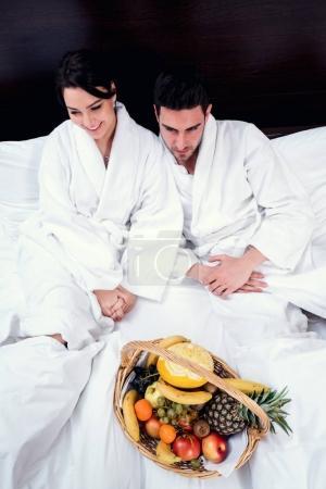 Photo pour Couple de détente au lit avec corbeille de fruits, plaisir - image libre de droit