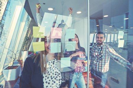 Photo pour Concept d'entreprise, de démarrage, de planification, de gestion et de personnes - heureuse équipe créative écrivant sur des autocollants sur un panneau de verre de bureau dans un bureau moderne - image libre de droit