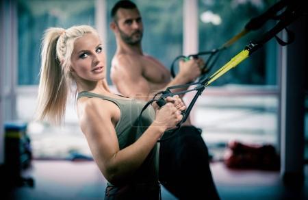 Photo pour Couple faisant push ups bras de formation avec trx sangles de remise en forme dans la salle de gym sport de mode de vie sain Concept d'entraînement - image libre de droit