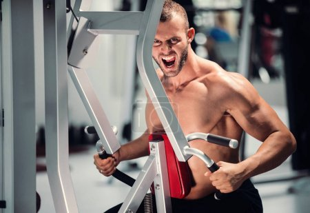 Photo for Determined young muscular man working on fitness machine at the gym - Royalty Free Image