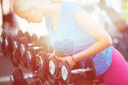 Photo for Strong female exercising with barbell in gym - Royalty Free Image