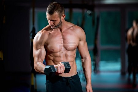 Photo for Handsome and strong man with beautiful body doing exercises in gym - Royalty Free Image