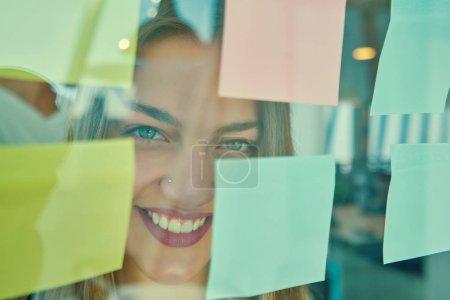 Photo pour Heureuse femme créative écrit sur des autocollants au bureau panneau de verre dans les bureaux modernes - image libre de droit