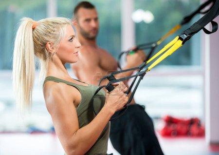 Photo pour Couple faisant push ups bras d'entraînement avec trx sangles de remise en forme dans la salle de gym Concept entraînement mode de vie sain sport - image libre de droit