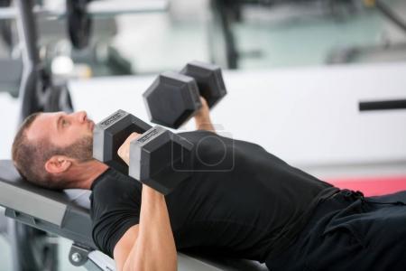 Photo pour Jeune mâle adulte beau faire des lignes d'haltère sur banc dans la salle de sport moderne - image libre de droit