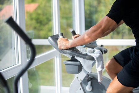 Photo for Young man exercise bike, cycling, stationary exercising. Indoors gym. - Royalty Free Image