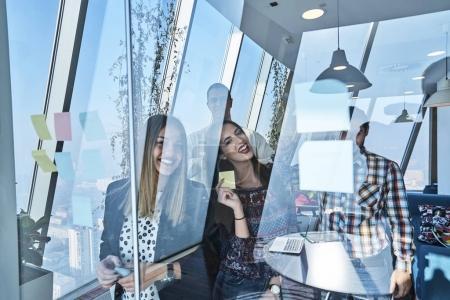 Photo pour Concept d'entreprise, de démarrage, de planification, de gestion et de personnes - heureuse équipe créative écrivant sur des autocollants sur un panneau de verre de bureau - image libre de droit