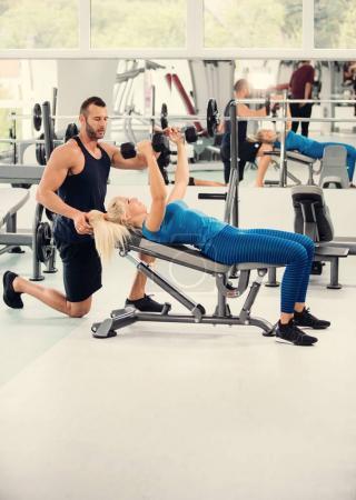 Photo pour Entraîneur personnel travaillant avec la jeune femme dans la salle de gym - image libre de droit