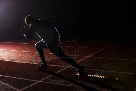 Photo for Sport. Sprinter leaving starting blocks on the running track. - Royalty Free Image