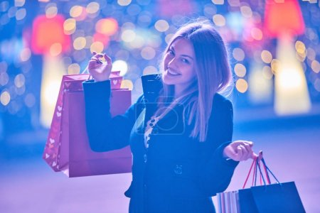 Foto de Hermosa mujer que llevaba muchas bolsas en una calle de la ciudad - Imagen libre de derechos