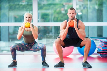 Kneeling muscular couple exercising with kettlebells at gym
