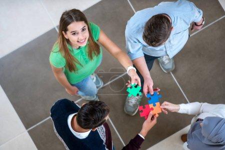 Photo pour Travail d'équipe de partenaires. Notion d'intégration et de mise en service avec les pièces du puzzle, les élèves, les collègues de travail - image libre de droit