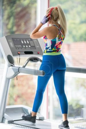 Photo for Sport, fitness, lifestyle, technology and people concept - woman with or player and earphones exercising on treadmill in gym - Royalty Free Image
