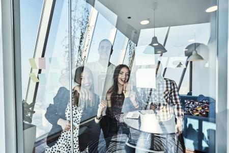 Photo pour Concept d'affaires, démarrage, planification, gestion et personnes - joyeuse équipe créative écrit sur des autocollants au Bureau verre panneau - image libre de droit