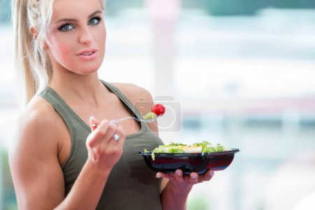 Photo for Healthy young woman eating vegetables green salad at gym - Royalty Free Image