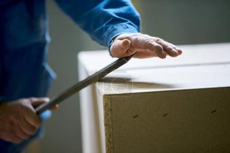 Young male worker  work in a factory for the production of furniture