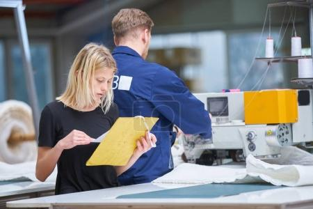 Photo for Seamstress is new assigned to a machine in a textile factory, the foreman explains something - Royalty Free Image