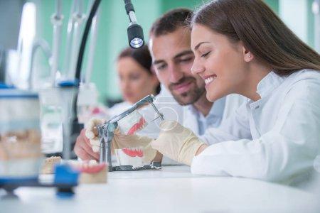 Photo pour Prothèses dentaires, hygiène bucco-dentaire. Mains de prothèses alors qu'il travaillait sur la prothèse dentaire, prothèses dentaires, une étude et une table avec des outils dentaires. - image libre de droit