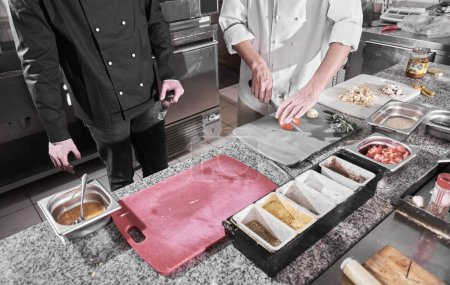 Photo for Chef sprinkling spices on dish in commercial kitchen - Royalty Free Image