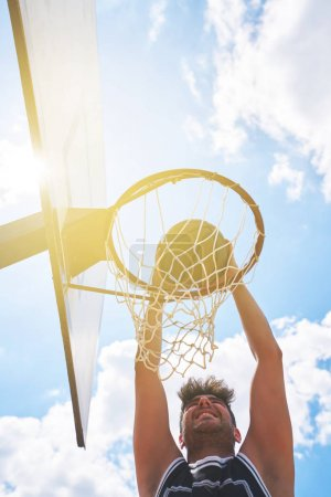 Photo for Basketball player in action flying high and scoring - Royalty Free Image
