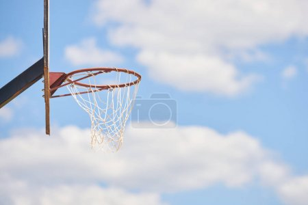 Basketball hoop in sunlight and sky