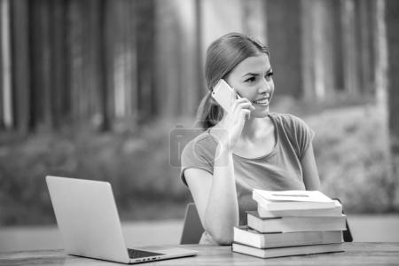 Photo for Young woman using laptop computer and smart phone. Beautiful student girl working on laptop and studying - Royalty Free Image
