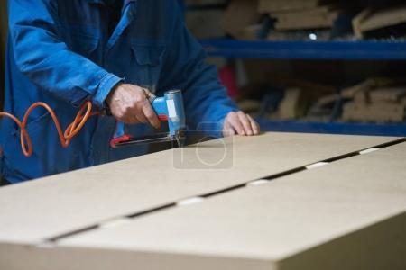Photo pour Jeune travailleur masculin travaillant dans une usine pour la production de meubles - image libre de droit