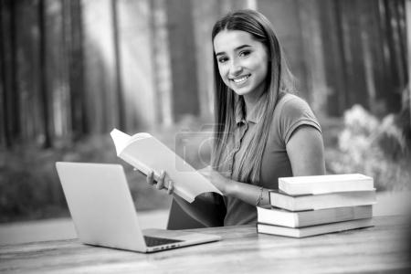 Young woman using laptop computer and smart phone. Beautiful student girl working on laptop and studying