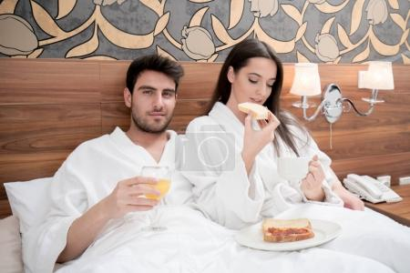 hotel, travel, relationships, and happiness concept - happy couple in bed