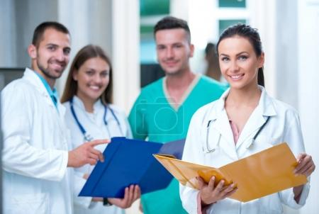 Photo for Clinic, profession, people, health care and medicine concept - happy group of medics or doctors at hospital corridor - Royalty Free Image