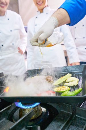 Photo for Chef in restaurant kitchen at stove with pan, doing flambe on food - Royalty Free Image