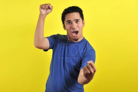 Photo for Young asian man happy and excited expressing winning gesture. Successful and celebrating on yellow background - Royalty Free Image