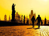 Foggy morning on Charles Bridge, Prague, Czech Republic. Sunrise with silhouettes of walking people, statues and Old Town towers. Romantic travel destionation