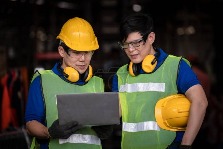 Photo pour Travailleur de l'industrie sous inspection et vérification du processus de production en usine par ordinateur portable, Ingénieur portant un uniforme décontracté et un casque de sécurité au travail - image libre de droit