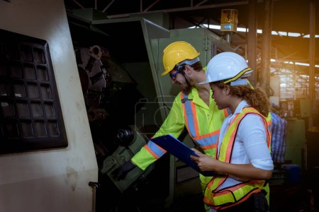 Photo pour Ingénieur industriel en cours d'inspection et de vérification du processus de production au poste d'usine par document à portée de main, Ingénieur portant un uniforme décontracté et un casque de sécurité - image libre de droit