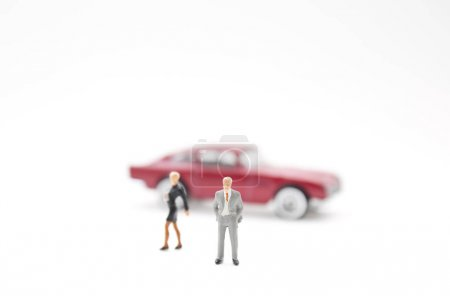 figures of businesspeople and toy car on white background